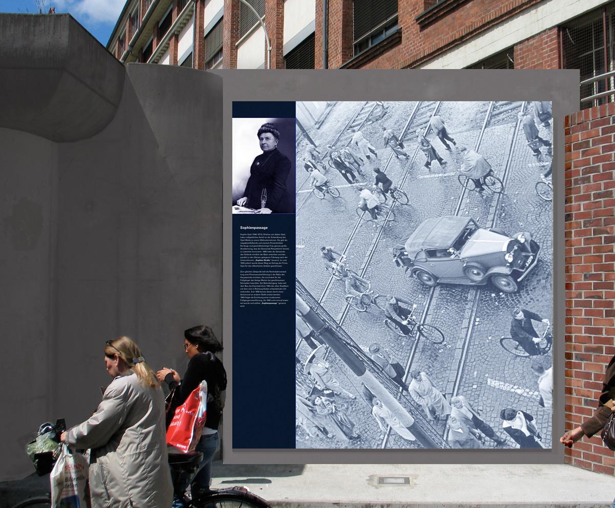 Informationstafel über Sophie Opel. Gelich neben dem alten Opelgebäude ist eine Bahnunterfürtung an der die tafel patziert ist. Früher war an gleicher Stelle ein Bahnübergang, der auf der Tafel abgebildet ist.